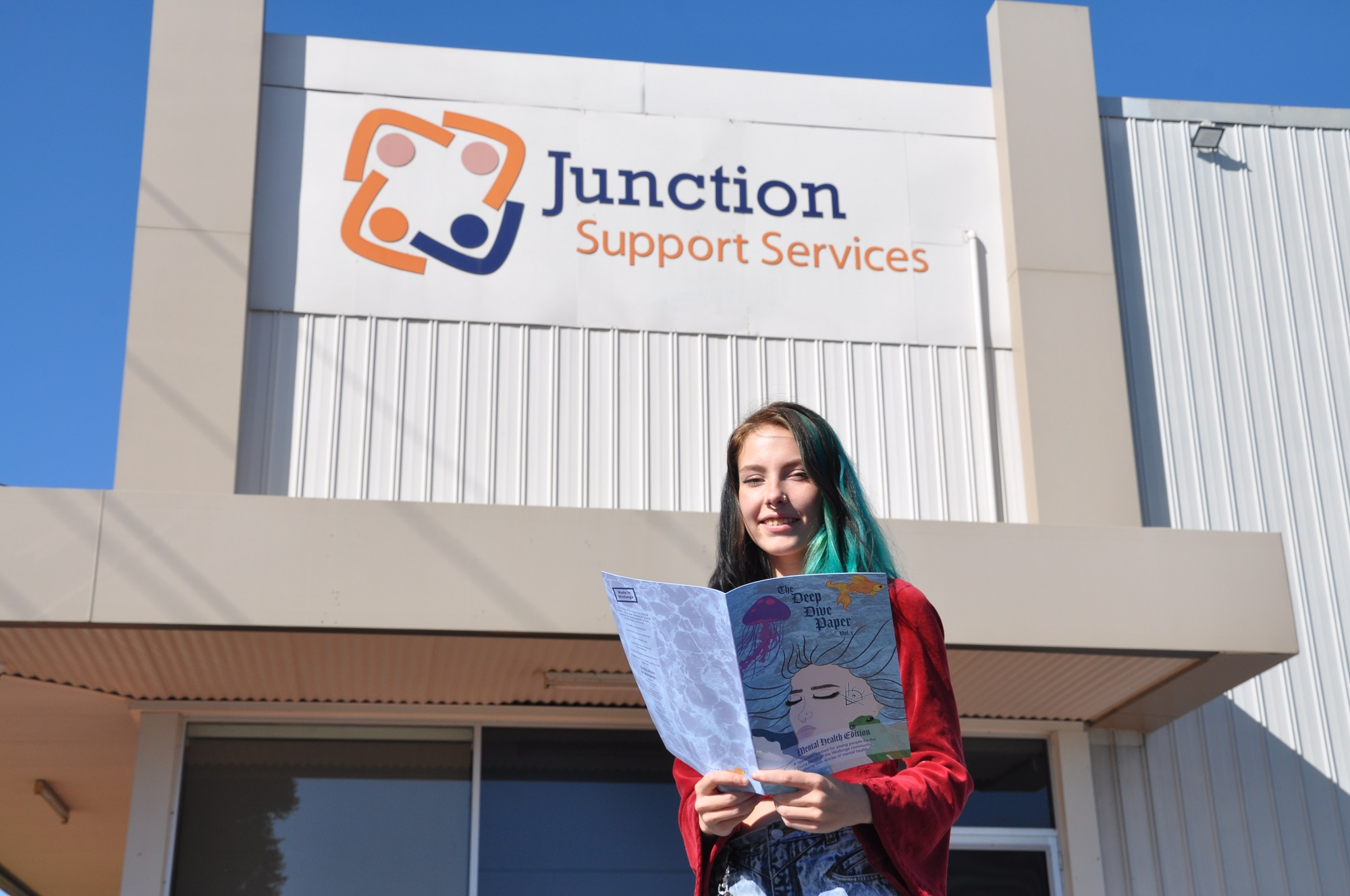 A young person reads Deep Dive outside of Junction Support Services